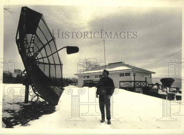 1986 Press Photo Carl Warner inspects satellite dish outside his New York home - Historic Images