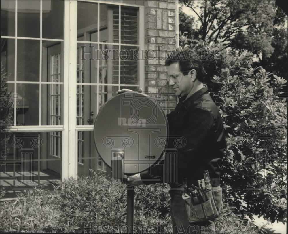 1994 Press Photo Unidentified man installing RCA DSS satellite dish outside home - Historic Images