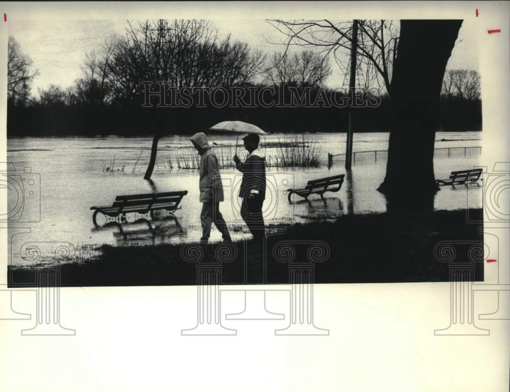 1987 Press Photo Couple strolls through flooded park in Schenectady, New York - Historic Images