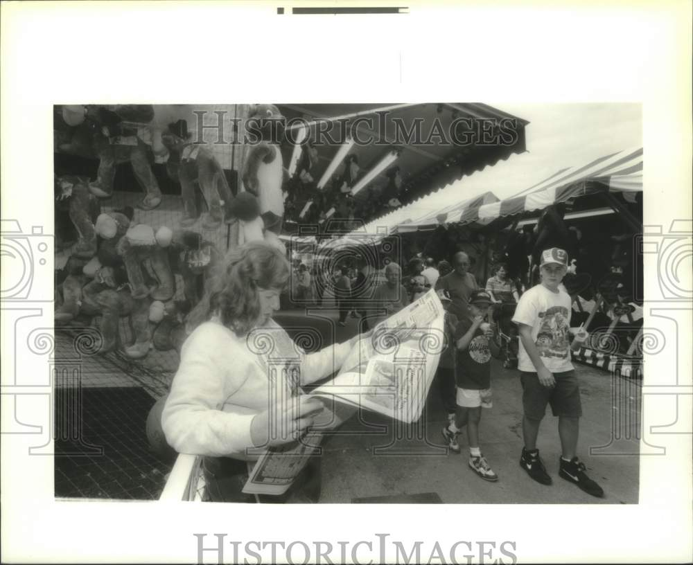 1994 Press Photo Concessioner reads newspaper at Schaghticoke, New York Fair - Historic Images