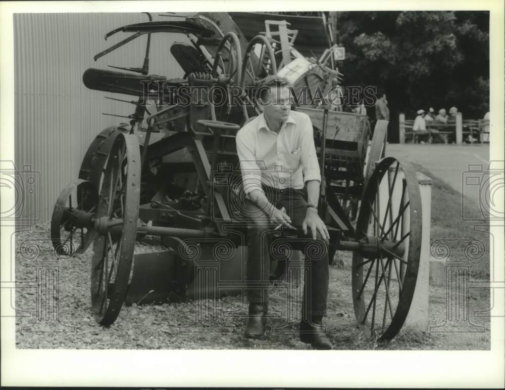 1993 Press Photo Schaghticoke, New York Fair visitor rests on old farm equipment - Historic Images
