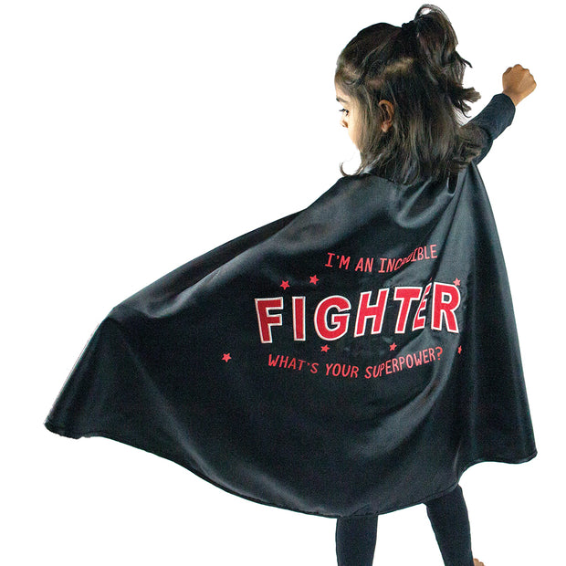little girl in open the joy's red and black cape designed to empower children fighting illness or disease