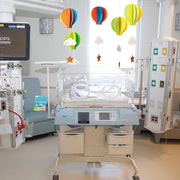 Open the Joy Hot air ballon room decor kit hanging over a premature baby bassinet in a hospital room in the nicu