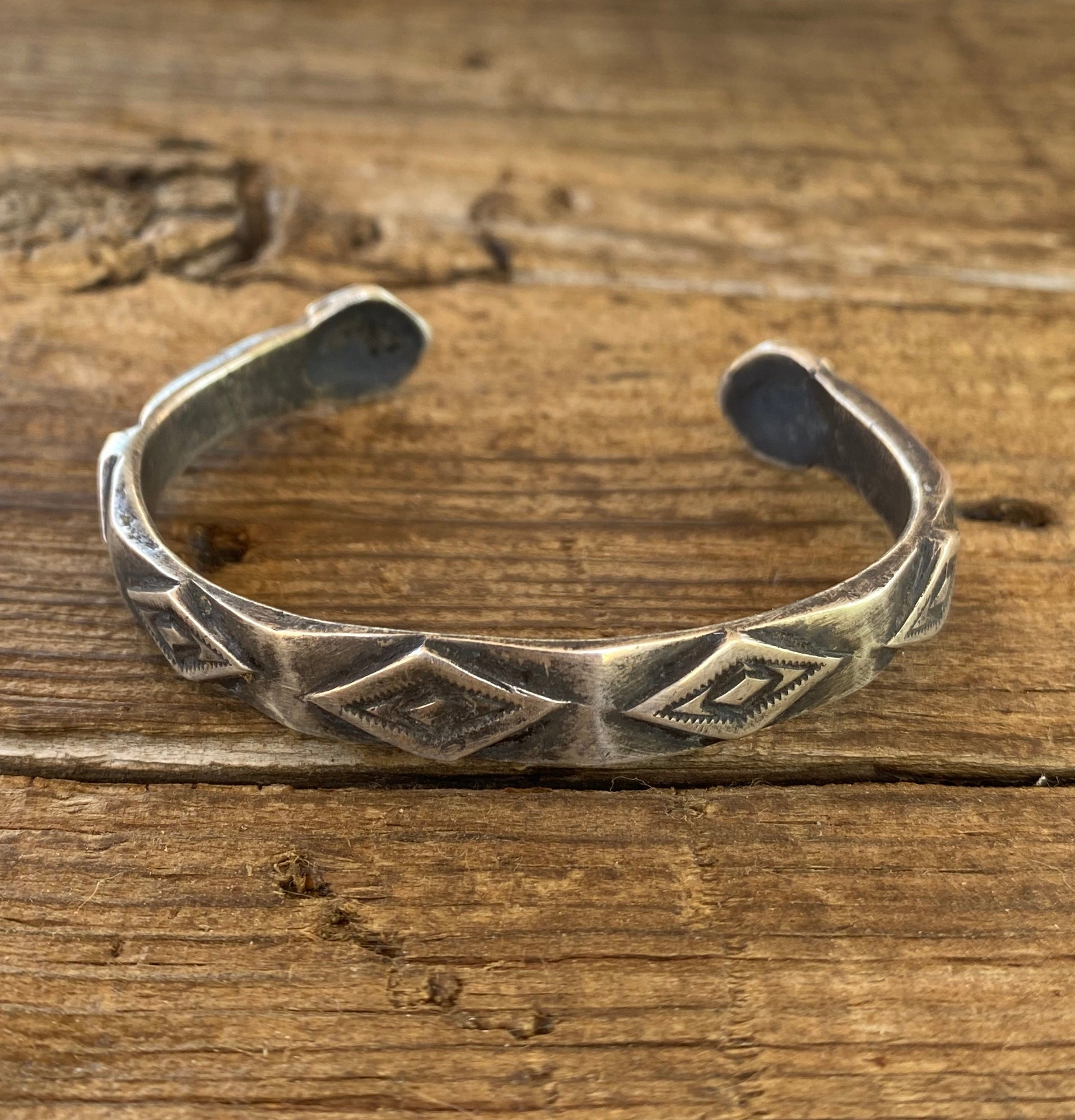 silver bracelet with two rattlesnake heads