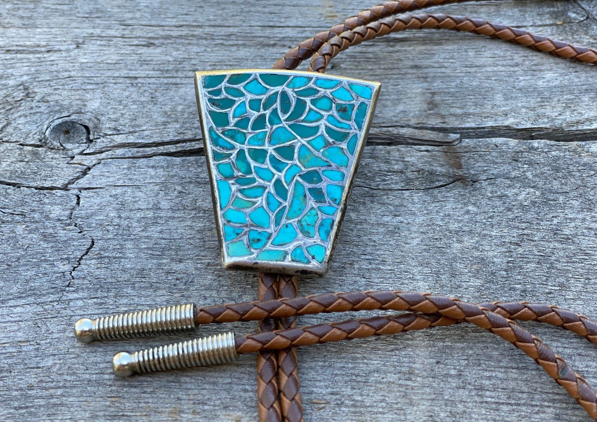 Silver and turquoise bolo tie on brown braided leather with silver tips