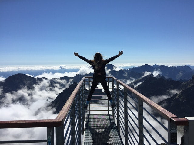 Woman on mountain top achieving goal