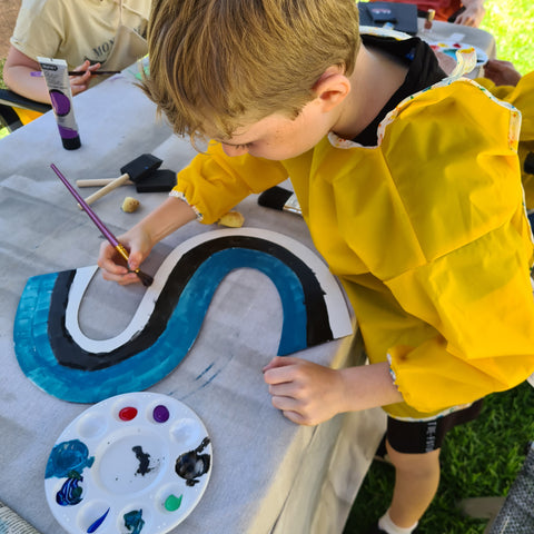 Child painting wood sign at Wandering Engraver Workshop
