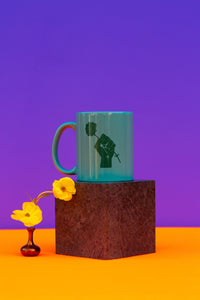 teal colored mug with fist and flower