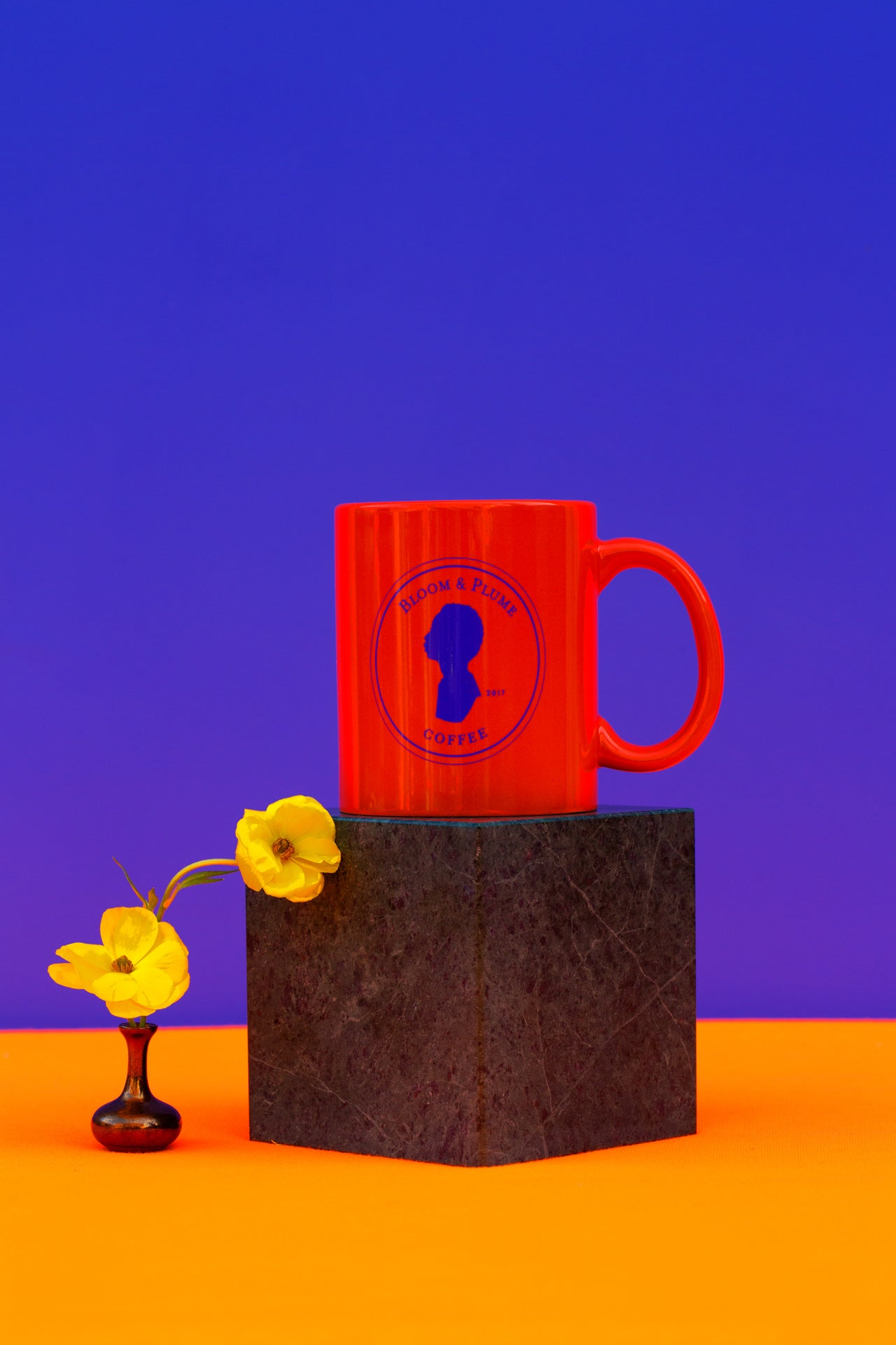 orange colored mug with bloom and plume seal