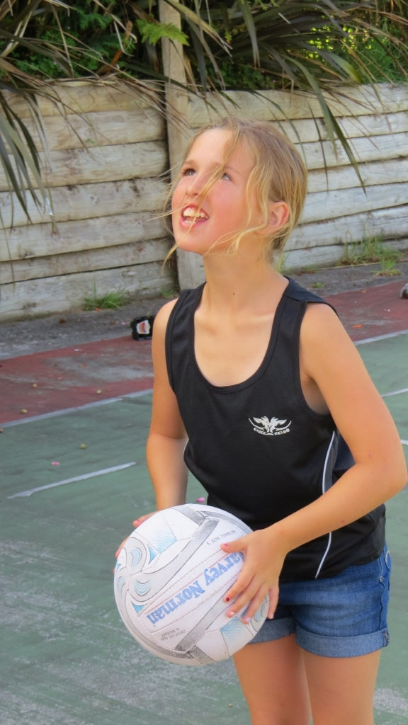 Girl wearing lightweight black quick dry singlet holding netball