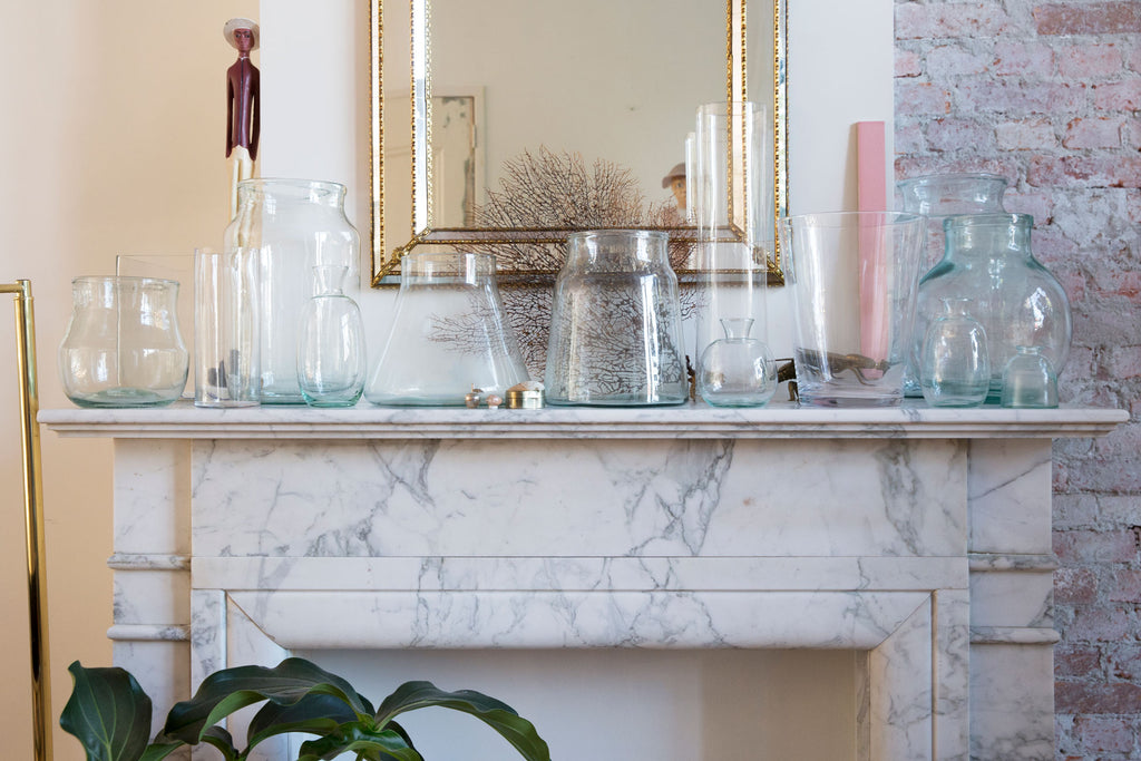 A marble fireplace with all bloomon vases on it