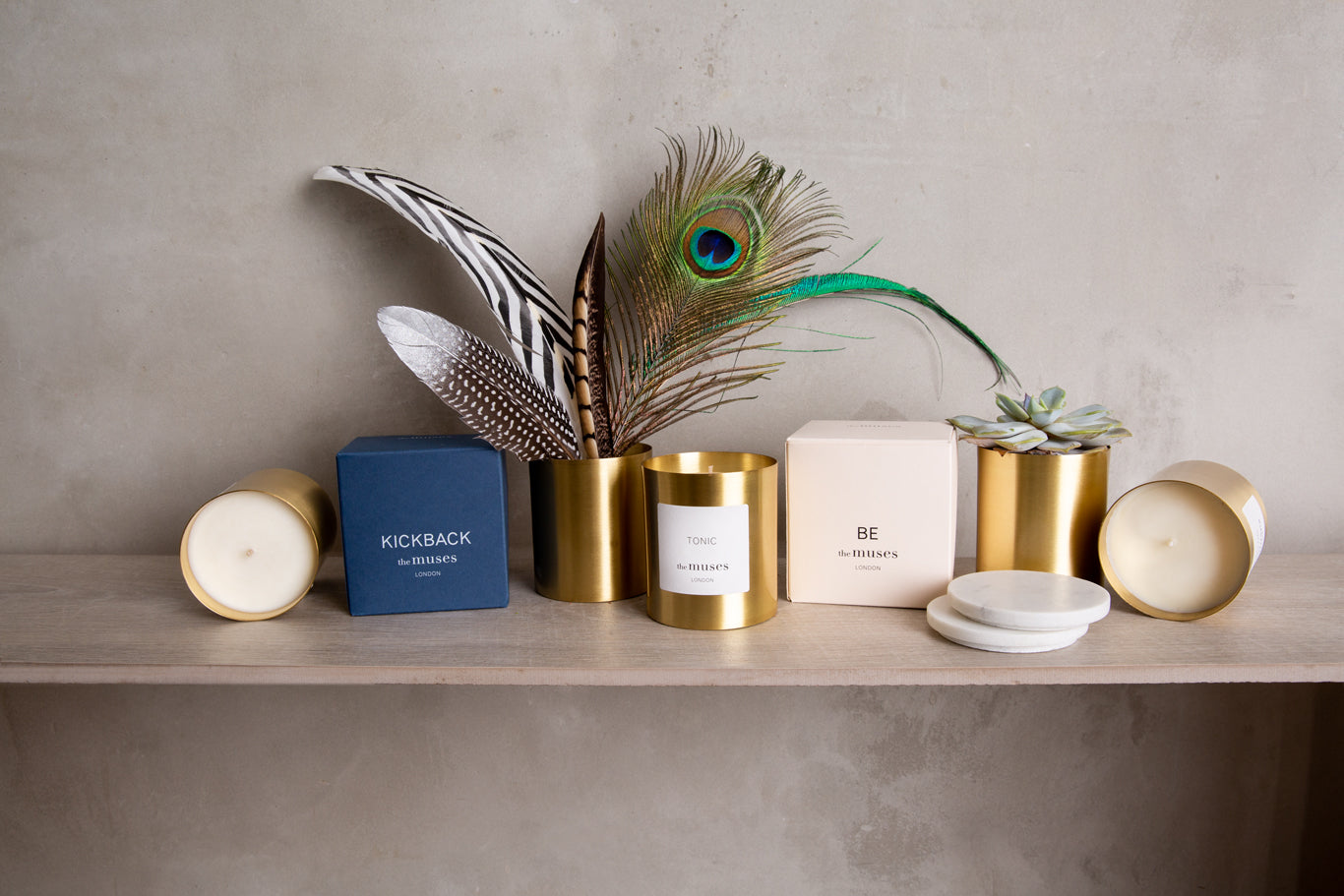 The Muses candles, boxes and containers on display with exotic feathers and marble lids