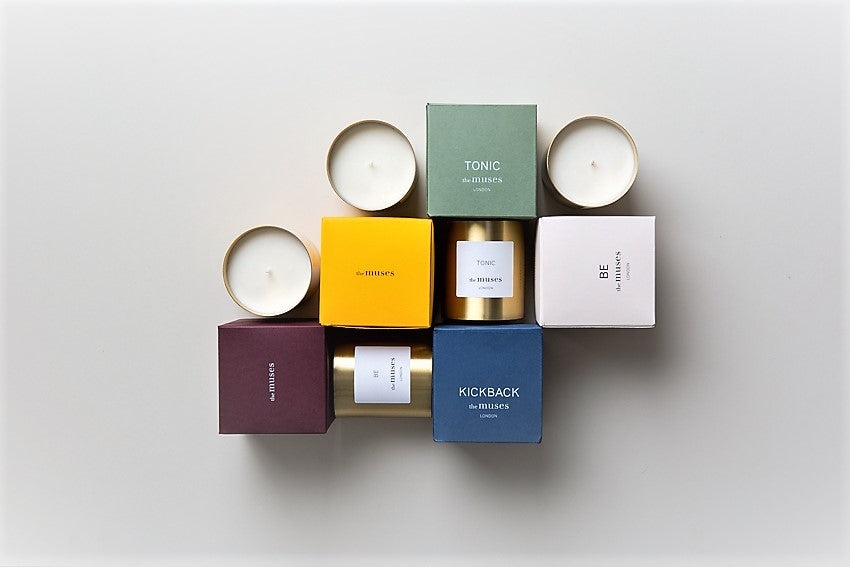 The Muses natural candle collection in an interesting arrangement with brass candle containers and colourful boxes