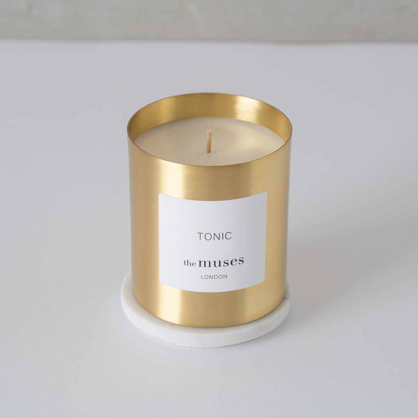 Tonic 100% natural wax candle in pure brass container on pure marble coaster. Front
