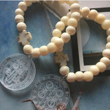White bone bracelets and medal of Saint Benedict