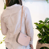 Jade convertible fanny pack from Kanevas, bag worn at the shouldert; light pink vegan leather and grey herringbones cotton