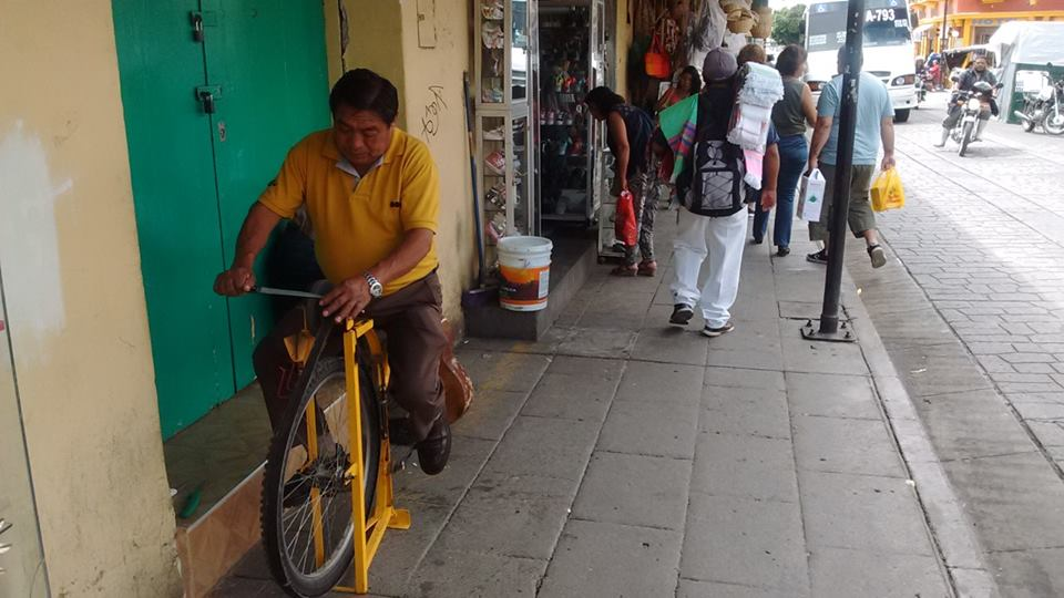 A man sharpening knives on a bicycle