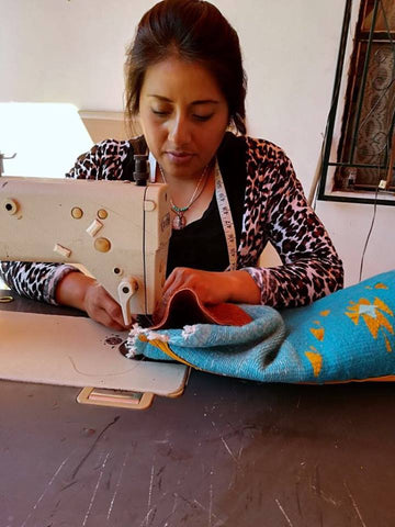 Marcela sewing a wool and leather backpack at her home near Oaxaca, Mexico