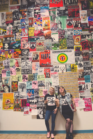 Two women stand in front of wall covered in punk music flyers.