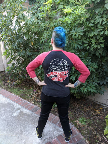 Person stands in front of green leafy bush, facing away from the camera to show the back of the Lactate With Love shirt - a lactation pump and a red banner with the text Lactate With Love. The person has tattoos on both forearms, shaved sides of their head and blue hair in a braid.