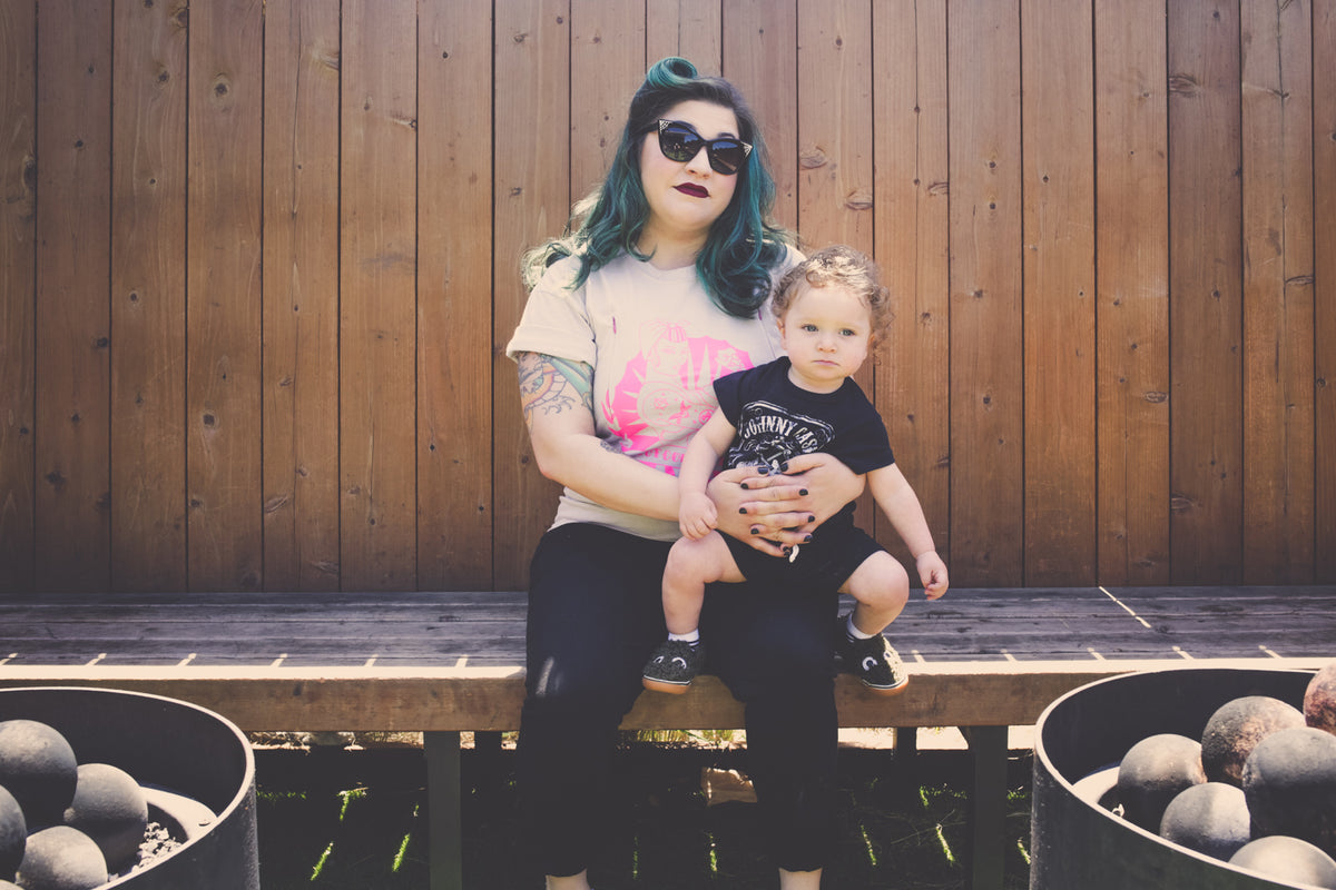 Punk mom with turquoise hair sits on bench with toddler on lap, both facing the camera. She is wearing an And Out Come The Boobs breastfeeding shirt.