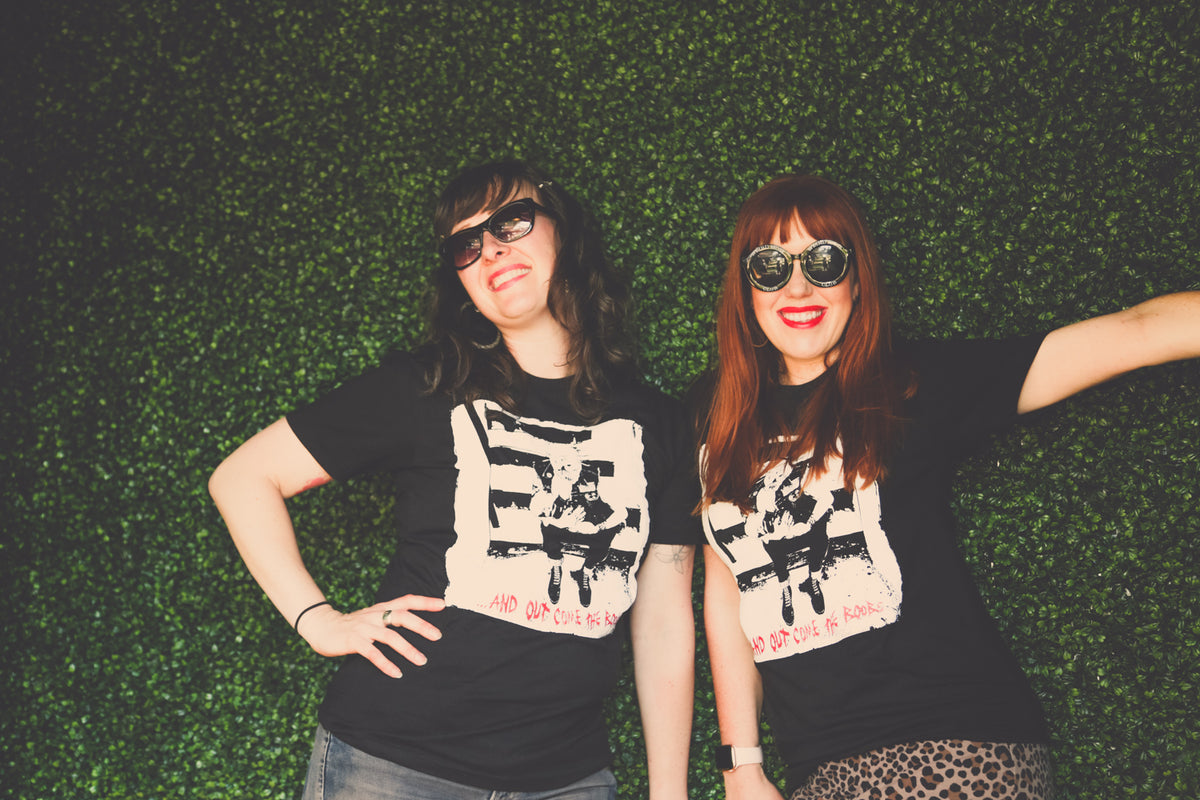 Two women pose in front of green, leafy wall. Both are wearing sunglasses and an And Out Come The Boobs breastfeeding shirt.