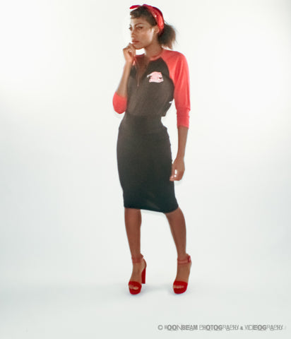 Black pin up style model stands in black pencil skirt, red heels, her hair in red bandana. She wears a black raglan shirt with red long sleeves, her right hand touches her mouth.