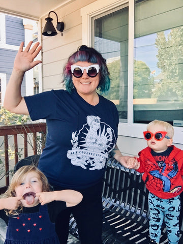 Mom wearing blue and white pin up breastfeeding shirt is waving at camera, she has a toddler either side of her, one pulling a funny face, the other in Wonder Woman sunglasses.
