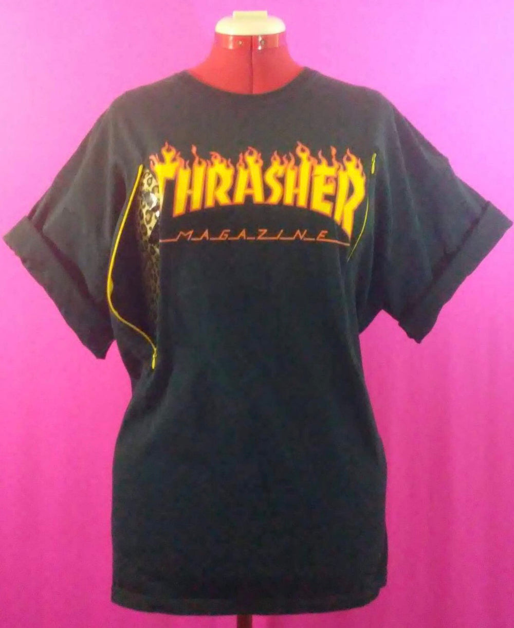 Black Thrasher T-shirt, logo is yellow with flame effect. Shirt is customized for breastfeeding and is on a mannequin against a pink backdrop