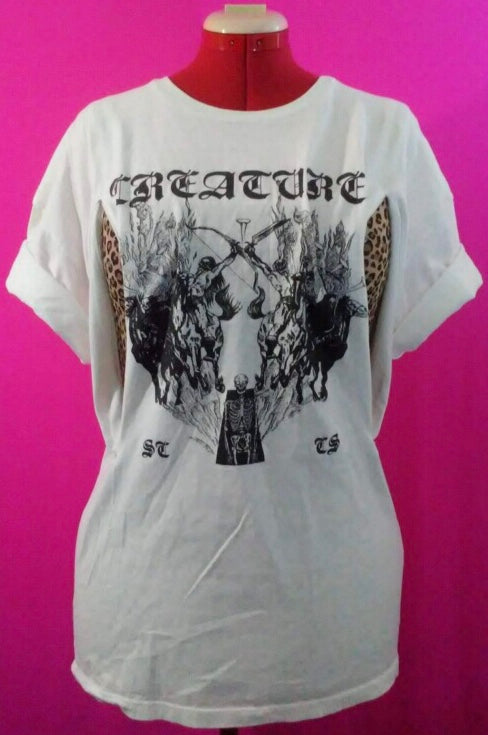 White shirt with black print from skate brand Creature. Image is medieval style drawing of  demons fighting. Shirt is on mannequin against pink background, and has been customized for breastfeeding