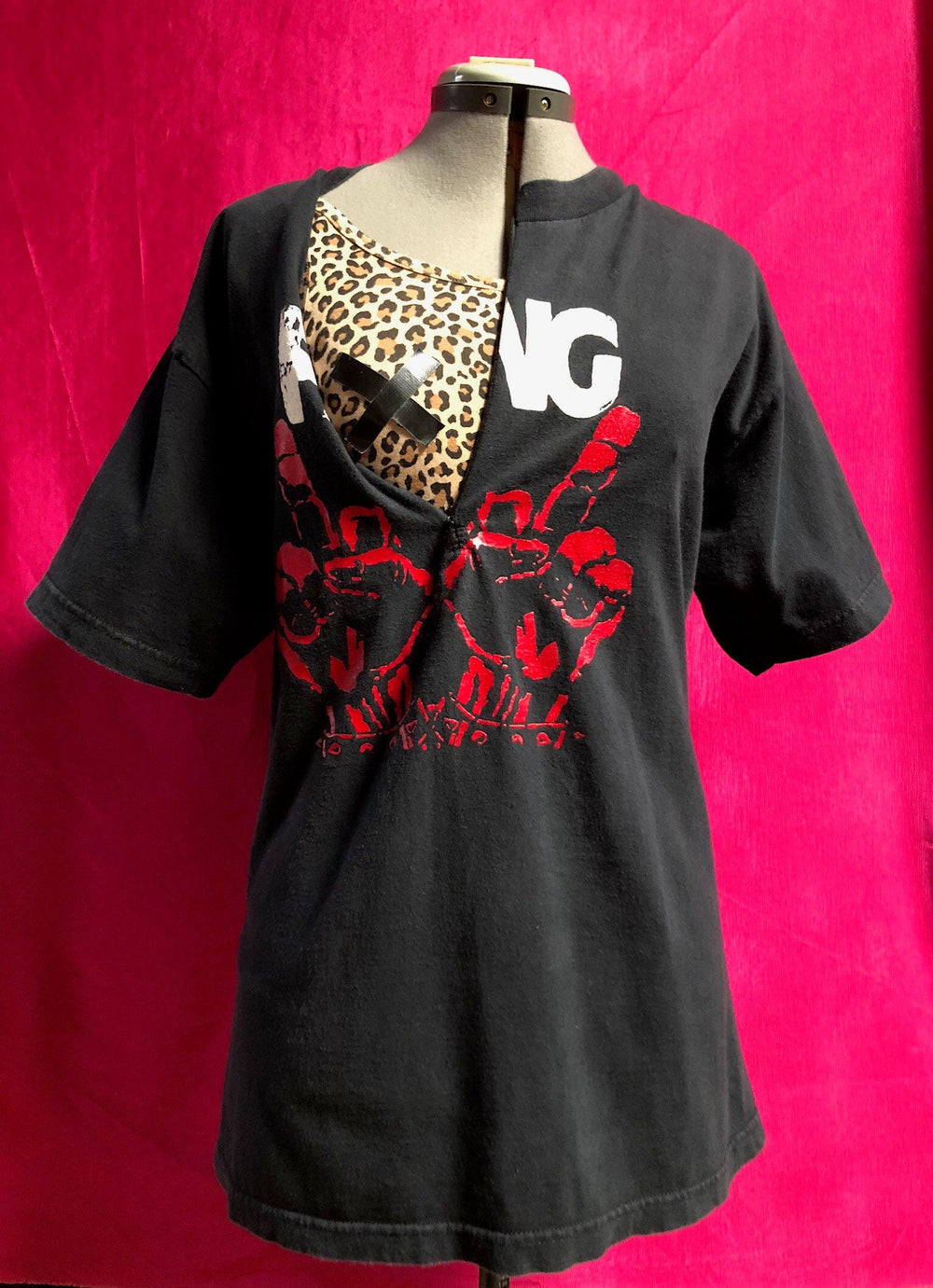 Black shirt with FANG design, customized for breastfeeding with zipper down front. In front of pink background.