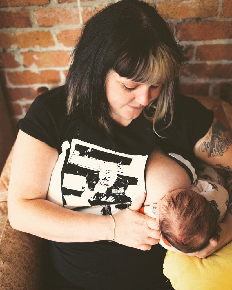 Punk mom breastfeeds infant wearing an And Out Come The Boobs breastfeeding shirt.
