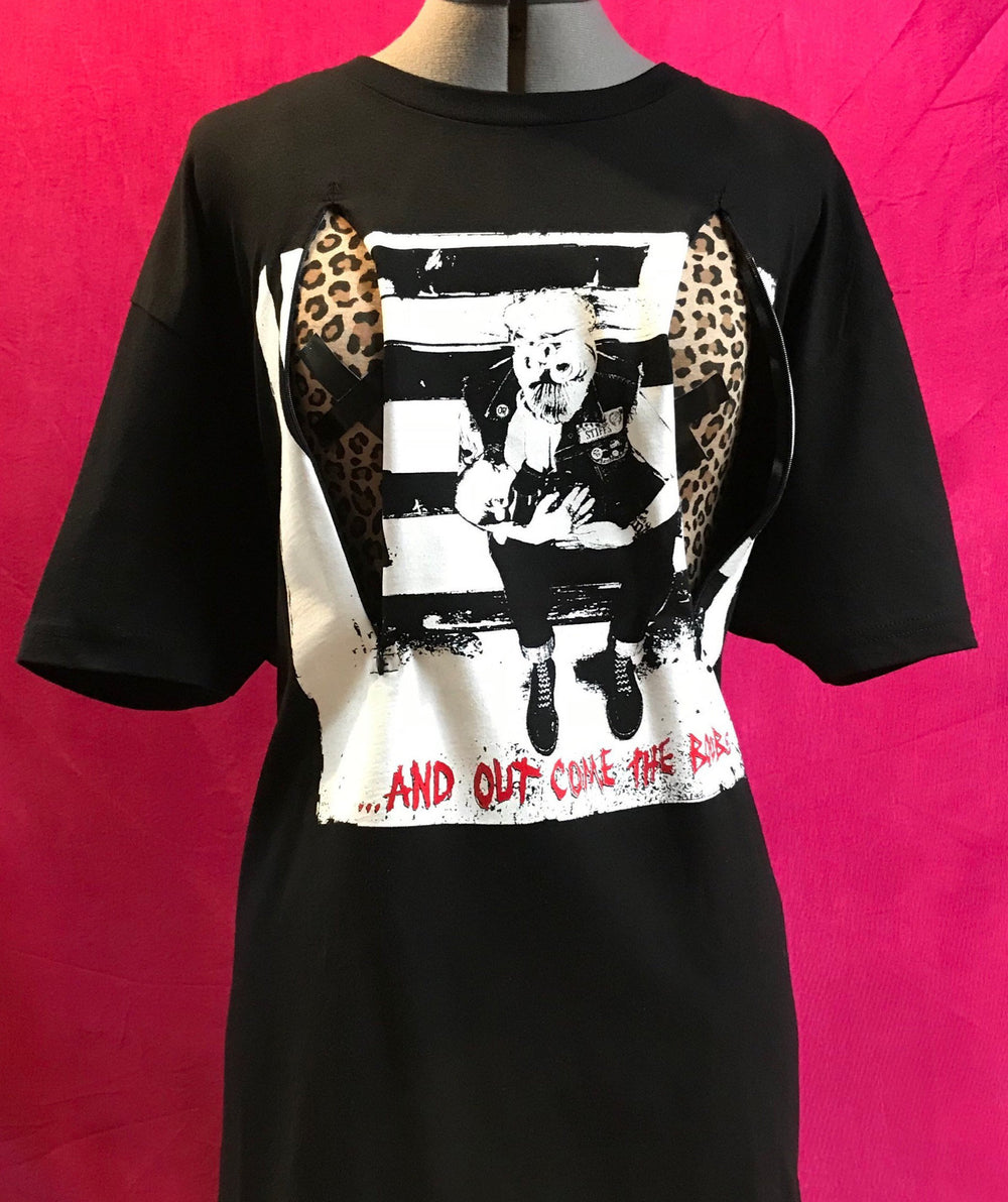 Black breastfeeding shirt on mannequin in front of pink background. Shirt has two zippers open in front to reveal leopard print mannequin underneath. Shirt has the classic And Out Come The Boobs logo printed on front, with breastfeeding punk mama and baby.