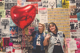 Two punk women fold hands in front of wall of punk posters. One is holding a red heart balloon. Both are wearing And Out Come The Boobs t-shirts.