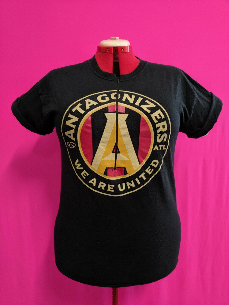 Black shirt in front of pink background, from band Antagonizers ATL. The shirt has been customized for breastfeeding with an invisible zipper.