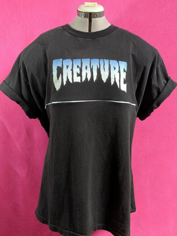 Black Creature shirt in front of pink background. Shirt has been customized for breastfeeding and has a zipper across the chest.