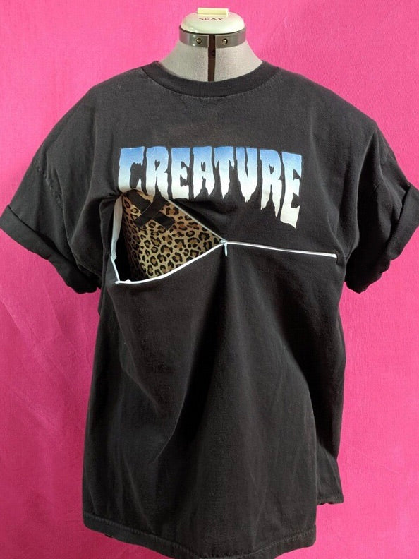 Black Creature shirt in front of pink background. Shirt has been customized for breastfeeding and has a zipper half-open across the chest.