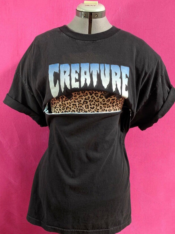 Black Creature shirt in front of pink background. Shirt has been customized for breastfeeding and has a zipper open across the chest.