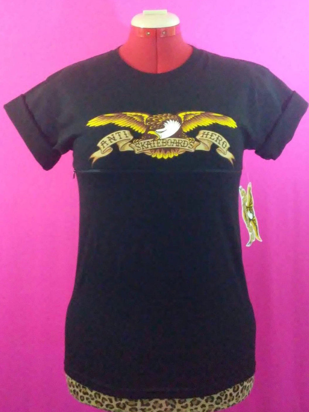 Black AntiHero shirt with eagle design in front of pink background. The shirt has been customized for breastfeeding with a zipper across the front.
