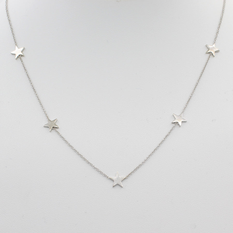 14k White Gold Five Station Star Necklace, front view of necklace displayed on mannequin neckline.