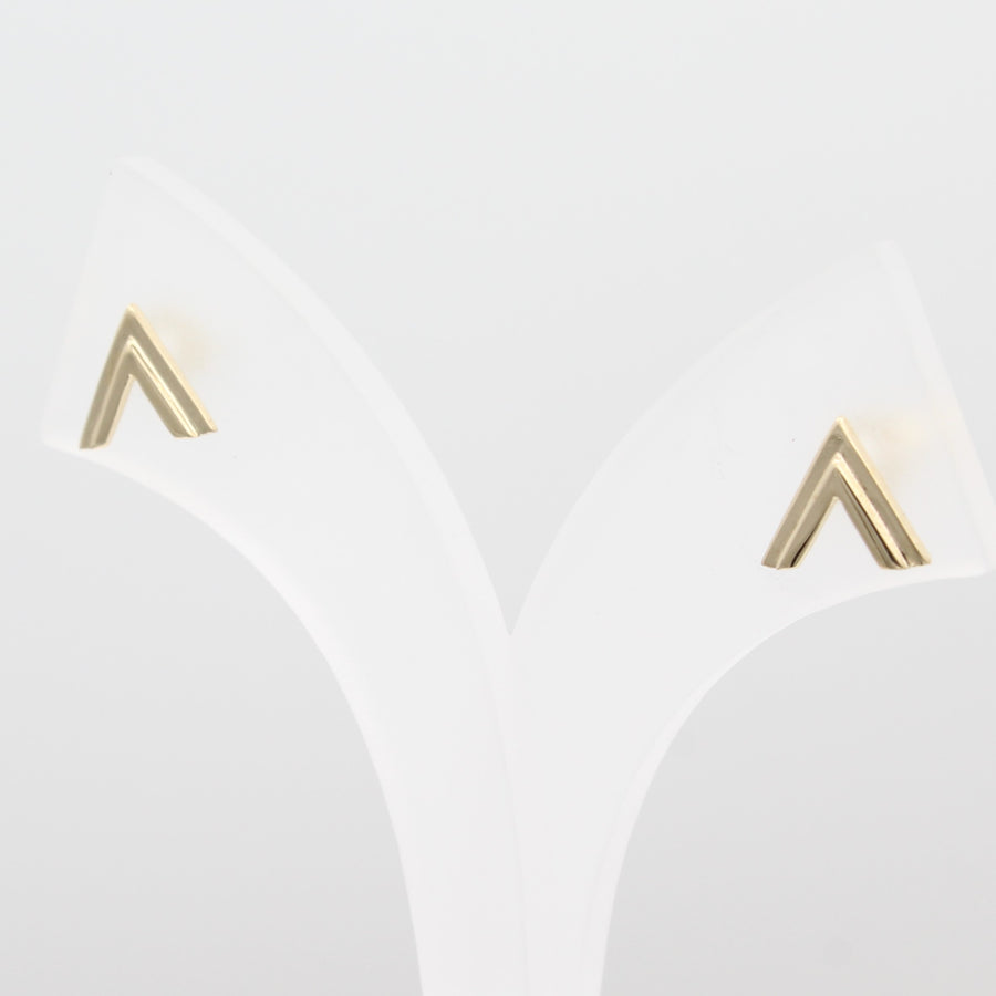 A close-up view of 14k Yellow Gold Double Chevron Earrings on a white jewelry display.