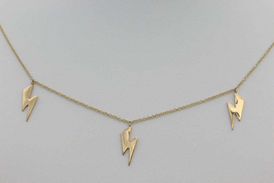 14k Yellow Gold Lightning Bolt Five Station Necklace, close-up front view of three of the necklace's five lightning bolt designs.