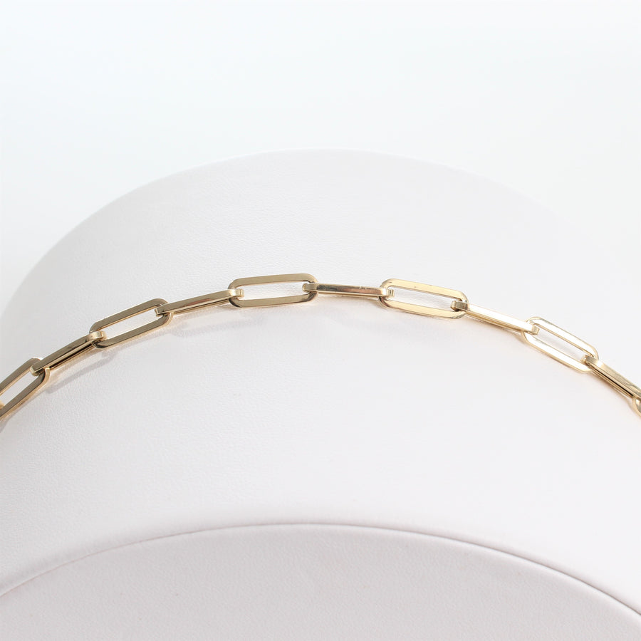 14k Yellow Gold Retro Elongated Link Paperclip Large Link Bracelet. close-up view of unclasped bracelet laid out on a white jewelry display.