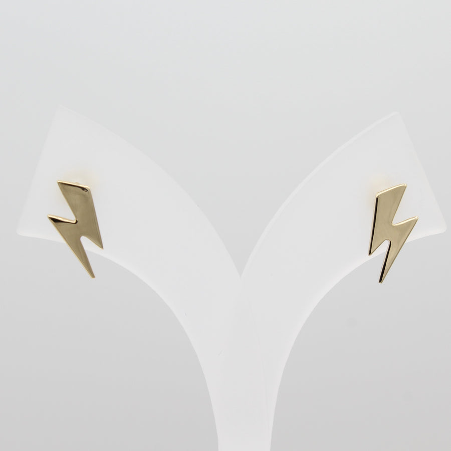 14k Yellow Gold Striking Lightening Bolt Earrings, front view of earrings on a white jewelry display.