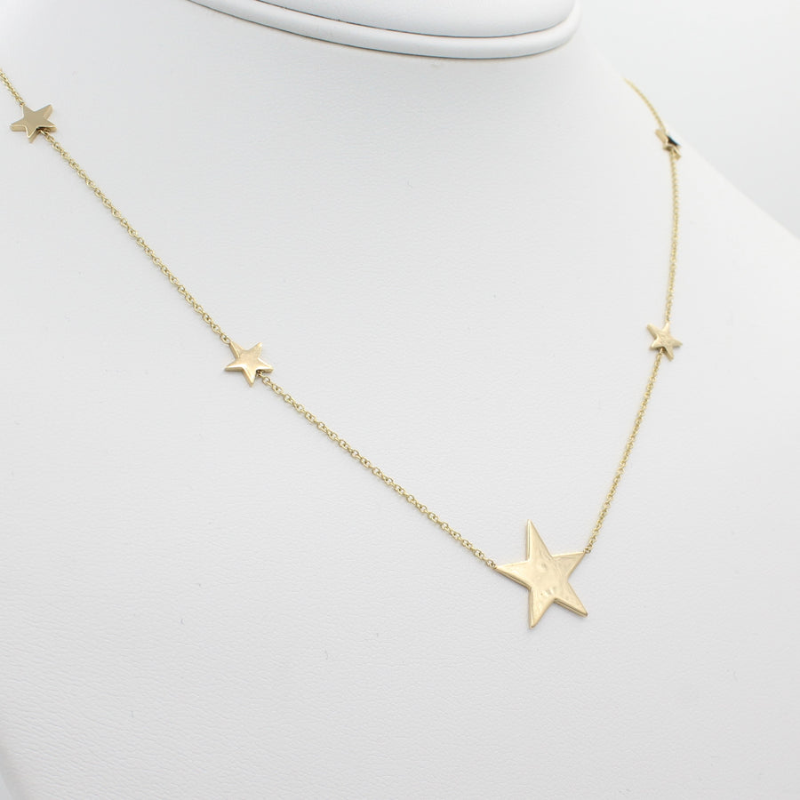 14k Yellow Gold North Star Five Station Necklace, close-up front view of necklace displaced on a mannequin neckline.