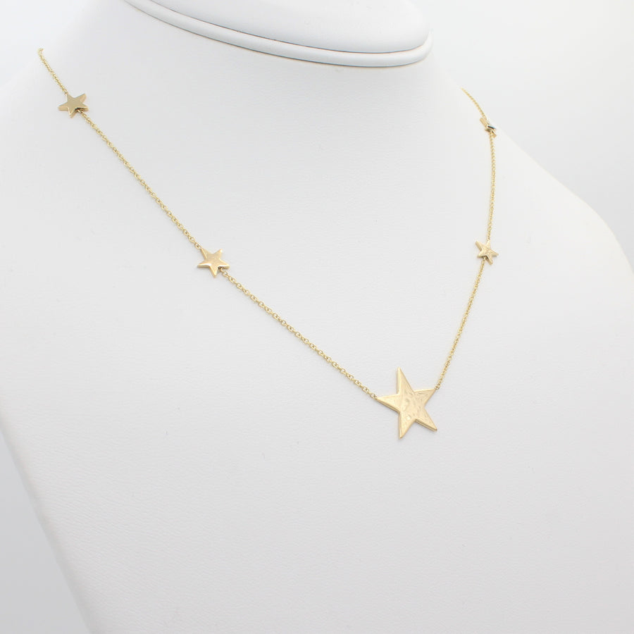 14k Yellow Gold North Star Five Station Necklace, front view of necklace displaced on a mannequin neckline.