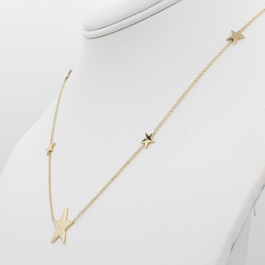 14k Yellow Gold North Star Five Station Necklace, right angle view of necklace displaced on a mannequin neckline.