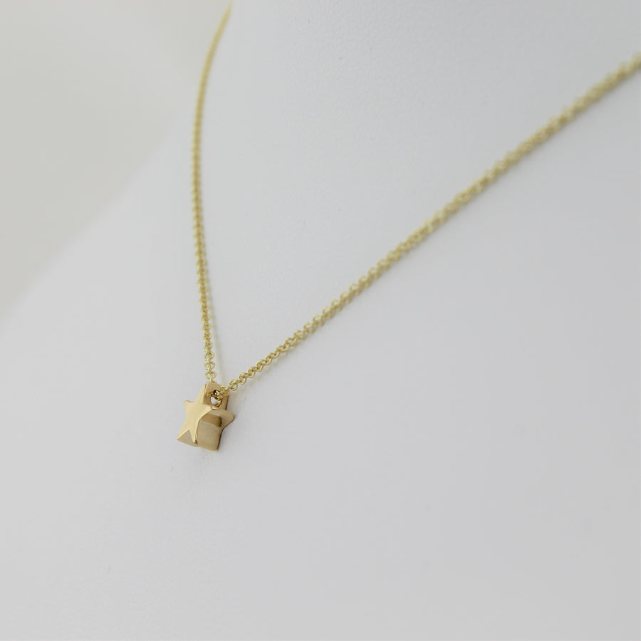 14k Yellow Gold Shining Star Pendant, close-up right angle view of the necklace displayed on a mannequin.
