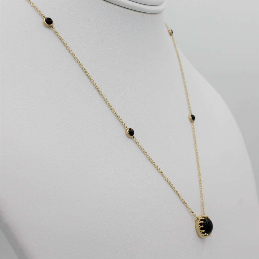 14k Yellow Gold Bewitched Black Onyx Station Necklace, left angle view of necklace displayed on a mannequin.