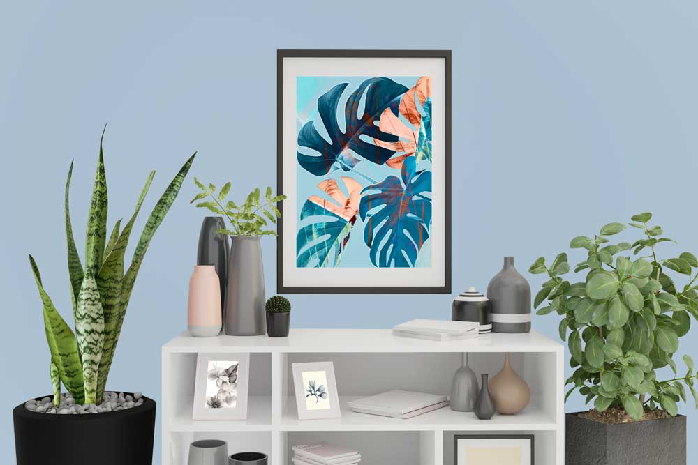 Claude & Leighton botanical blue Monstera Leaves art print hanging on a Dulux Bright Skies blue wall